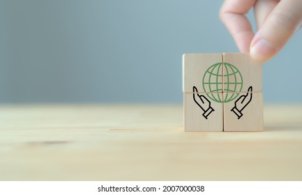 Social responsibility core value concept with hand and globe icon on cubes. CSR , eco green sustainable living, zero waste, plastic free, earth day, world environment day, responsible consumption.