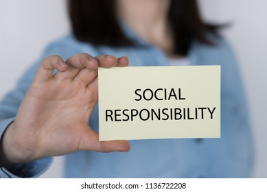 SOCIAL RESPONSIBILITY message on a yellow card hold by a business woman, business concept image with soft focus background