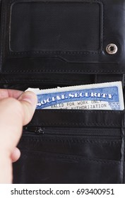 Social security card in simple black wallet, slightly sticking out.