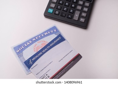 Social Security and Medicare card with a calculator for calculating cost on May 26, 2019