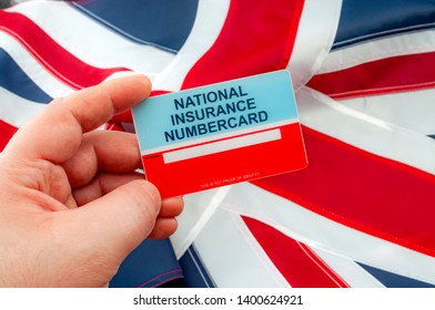 Social security system, access to safety net programs in Great Britain concept theme with a blank National Insurance Number card or NINO held in one hand with the UK flag in the background