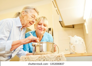 Social service Woman and senior citizen in the kitchen of the senior citizens apartment while cooking