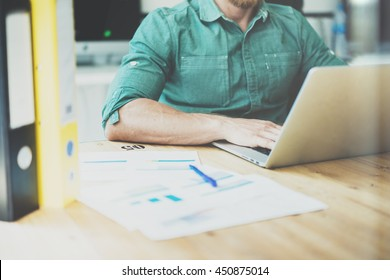 Social Trading Online Public Relations Manger Analyze Reports.Guy working wood table Modern Interior Office.Businessman Work Coworking Studio.Using Digital Laptop.Blurred Background.Business Startup