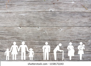 Social welfare concept on wooden background with families, old man, disabled, pregnant and woman with baby