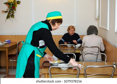 Social worker cleaning the table from dirty dishes after poor old people had free dinner. Opening the center of social services of Pechersky district. April 6, 2018. Kiev, Ukraine