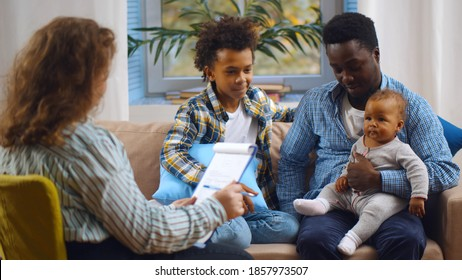 Social worker consulting smiling young single father with kids at home. Case worker woman visiting african man with schoolboy son and baby daughter providing consultation