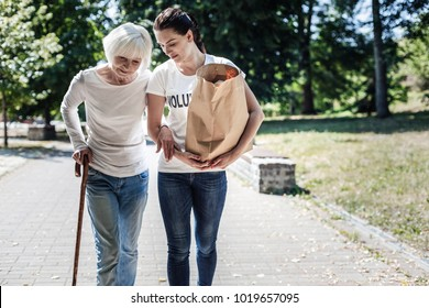 Social worker. Nice pleasant young woman holding a bag and carrying it while helping the elderly woman