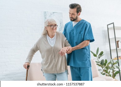 social worker supporting senior woman in eyeglasses with walking stick