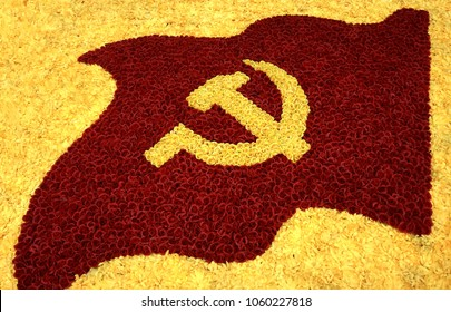 Socialistic symbol - hammer and sickle. Flower background yellow and red