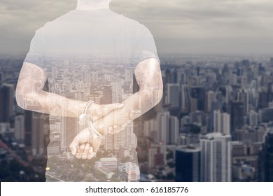A society full of danger concept - Hand young man in shackle on background blur The modern buildings of the city skyscrapers and leave space for adding your content.