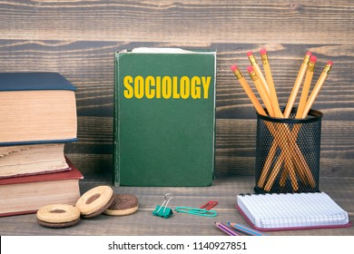 Sociology concept. Book on a wooden background.