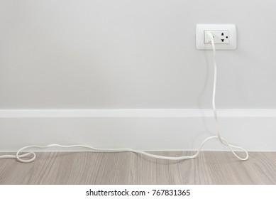 socket plug with electric plug line on white wall, interior design