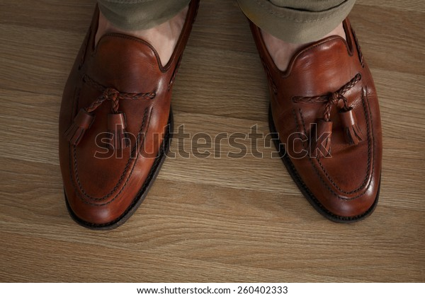 Sockless male legs in tasseled loafers, dark leaf colored and burnished. Preppy style dressed man wearing cushioned pants and loafers