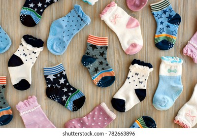Socks for children. View from above. Clothes for children in the form of socks. Knitted warm baby clothes. Multi-colored socks for girls and boys. Socks scattered on the table. Clothing for kids.