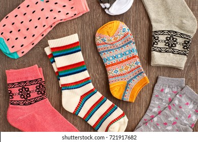 Socks for the cold season. View from above. Multicolored socks are scattered on a wooden background. Socks of fine jersey. Many different colorful socks. Clothes for autumn and winter.