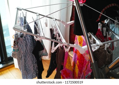 socks, underpants, towel and various clothes drying on clothes airer at home