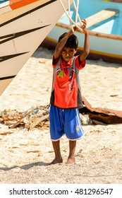 SOCOTRA, YEMEN - JAN 12, 2014: Unidentified Yemeni little boy plays hanging on a boat on the beach of the Island of Socotra. Children in Socotra live in poverty and grow without education