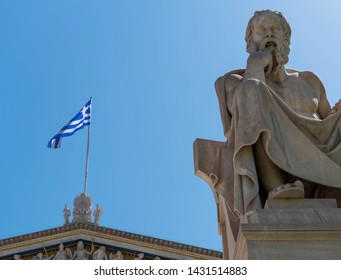 Socrates the Greek philosopher marble statue and Greek flag under clear blue sky, Athens Greece