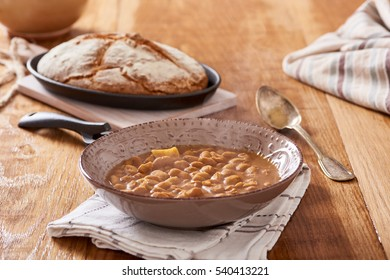 soda bread  on a oval cast iron pan and bean soup over a wooden table