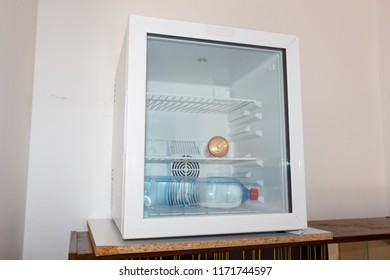 Soda can and water bottle in a mini-fridge with glass door in an hotel