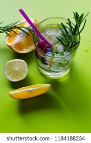 Soda drink with lime, orange and wild berries on a green background. From top view