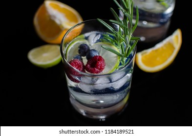 Soda drink with lime, orange and wild berries and mint on a black background From top view