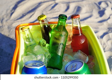 Soda drinks and filled ice cubes in a coolbox on the beach sand.