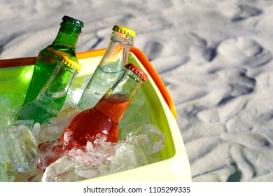 Soda drinks glass bottles and filled ice cubes in a coolbox on the beach sand.