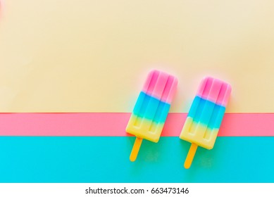 Soda and Strawberry and Lemon popsicle / ice cream stick on white, blue and pink background