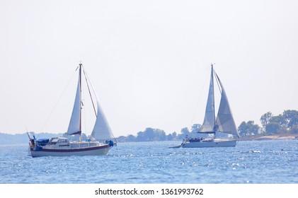SODERARM, SWEDEN - JUL 18, 2018: Two sailship on the blue ocean in the swedish archipelago, islets in the background. July 18 2018, Stockholm, Sweden