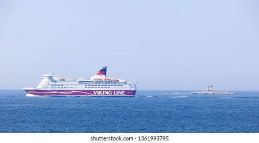 SODERARM, SWEDEN - JUL 18, 2018: Sailship and a passenger ferry on the blue ocean in the swedish archipelago, islets in the foreground. July 18 2018, Soderarm, Sweden