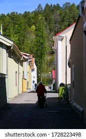 Soderkoping, Sweden May 10, 2020 A senior woman with a walker on a sidestreet.