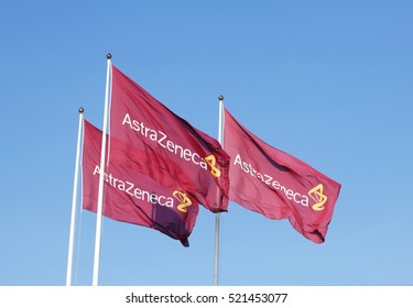 Sodertalje, Sweden - April 27, 2014: Three purple flags with the logo for Atrazeneca flying in the wind on top of the flagpoles against the blue sky.