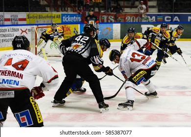 Sodertalje, Sweden - January 15, 2017: Face-off referee putting a puck between two ice hockey players in Ice hockey match in hockeyallsvenskan between SSK and MODO in the sports complex Scaniarinken