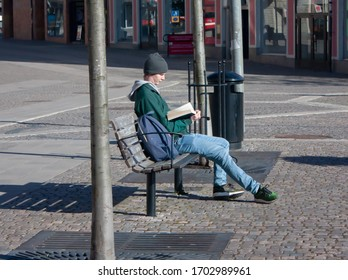 """Sodertalje/Sweden - April 2020: A young man sitting lonely on a park bench and reading a book on a sunny spring morning."""