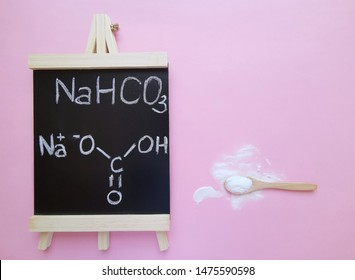 Sodium bicarbonate molecule, known as baking soda. Structural chemical formula written on a black chalkboard with spoonful of bicarbonate powder. NaHCO3  is a salt composed of Na, H, C and O atoms.