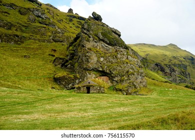 Sod-roof house under rock near Skógafoss