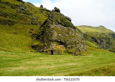 Sod-roof house under rock near Skógafoss