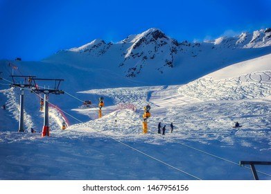 SOELDEN, AUSTRIA, January 09 2018: A view from ski lift over ski slopes with skiers and grooming machine in work during late afternoon in Soelden, Austria.