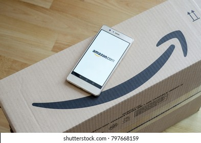 Soest, Germany - January 8, 2018: Amazon logo printed on cardboard box with Amazon logo on screen of Huawei P9 lite. Amazon.com, Inc., is an American electronic commerce and cloud computing company.