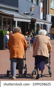 SOEST, NETHERLANDS - April 11, 2016. Two elderly ladies are walking and shopping with wheeled walker rollators at pedestrian zone in outdoor street with shops and stores. Aging populalation.