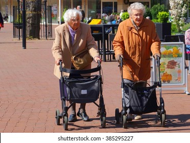 SOEST, NETHERLANDS - April 11, 2016. Two elderly women are walking together with wheeled walker rollators in shopping street of Dutch village.