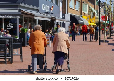 SOEST, NETHERLANDS - April 11, 2016. Two elderly women are shopping and walking with wheeled walker rollators in outdoor street with retail shops and stores. Holland, Province Utrecht.