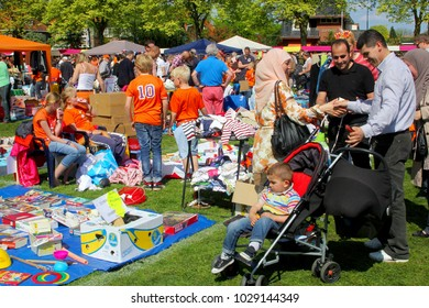 SOEST, NETHERLANDS - April 27, 2017. Mother, father and little son in buggy are looking for secondhand children games and used toys at traditional Vrijmarkt flea market on Koningsdag (Kingsday).