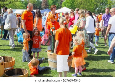 SOEST, NETHERLANDS - April 27, 2017. Father,  his little daughters and other children in orange clothes are watching an old water pump at outdoor Vrijmarkt flea market on King's Day (Koningsdag).