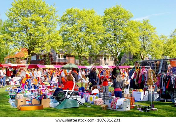 SOEST, NETHERLANDS - April 27, 2017. Crowds of Dutch people buy and traders sell secondhand stuff and used goods at  outdoor Vrijmarkt flea market on Koningsdag (Kingsday, Kings Day). Near Amsterdam.