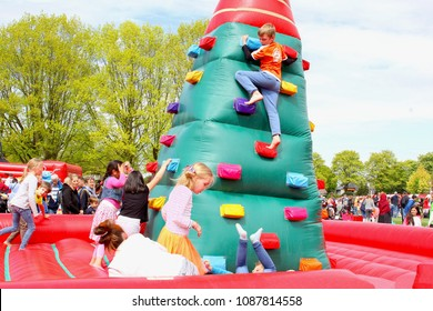 SOEST, NETHERLANDS - April 27, 2018. Group of Dutch children are playing together in bouncing castle and are climbing tower walls in outdoor playground park on Koningsdag (Kingsday). Birthday of King.