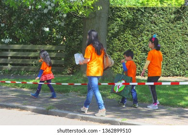 SOEST, NETHERLANDS - April 27, 2018. Integrated Asian family, mother and three children, are walking in the street to the Vrijmarkt flea market in traditional orange shirts on Koningsdag (Kingsday).