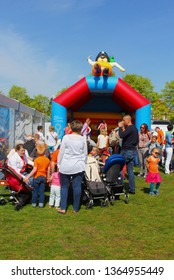 SOEST, NETHERLANDS - April 27, 2018. Families with babies in stroller are having fun, watching children playing in bouncing castle in outdoor park.