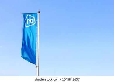 SOEST, NETHERLANDS - February 28, 2018. Blue waving flag with white AH logo of supermarket grocery store Albert Heijn in a blue sky.